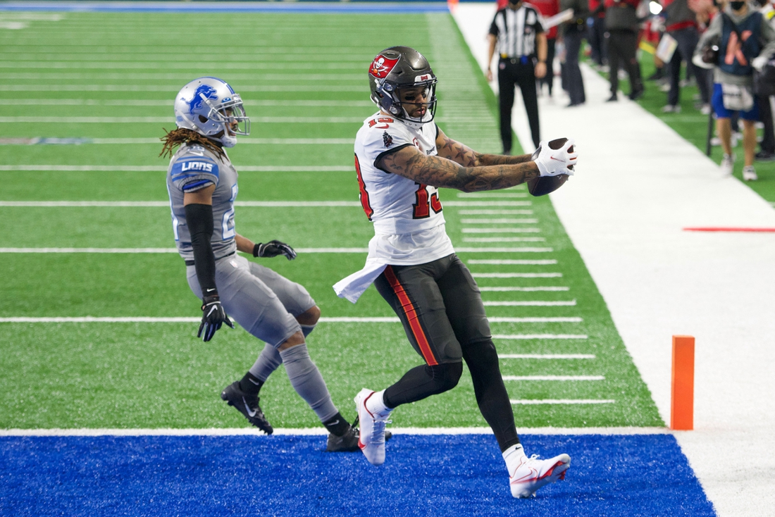 Dec 26, 2020; Detroit, Michigan, USA; Tampa Bay Buccaneers wide receiver Mike Evans (13) scores a touchdown as Detroit Lions cornerback Darryl Roberts (29)  pursues during the third quarter at Ford Field. Mandatory Credit: Tim Fuller-USA TODAY Sports