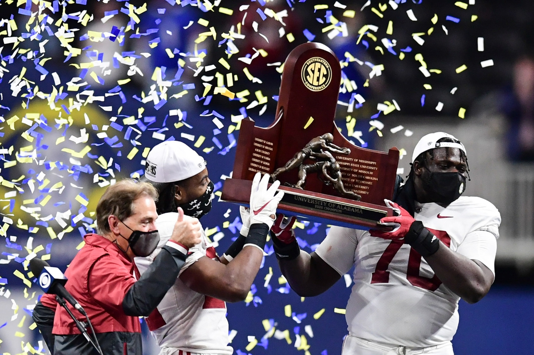 Dec 19, 2020; Atlanta, Georgia, USA; Alabama Crimson Tide head coach Nick Saban running back Najee Harris (22), and offensive lineman Alex Leatherwood (70) celebrates with the SEC Championship trophy after beating the Florida Gators in the SEC Championship at Mercedes-Benz Stadium. Mandatory Credit: Adam Hagy-USA TODAY Sports