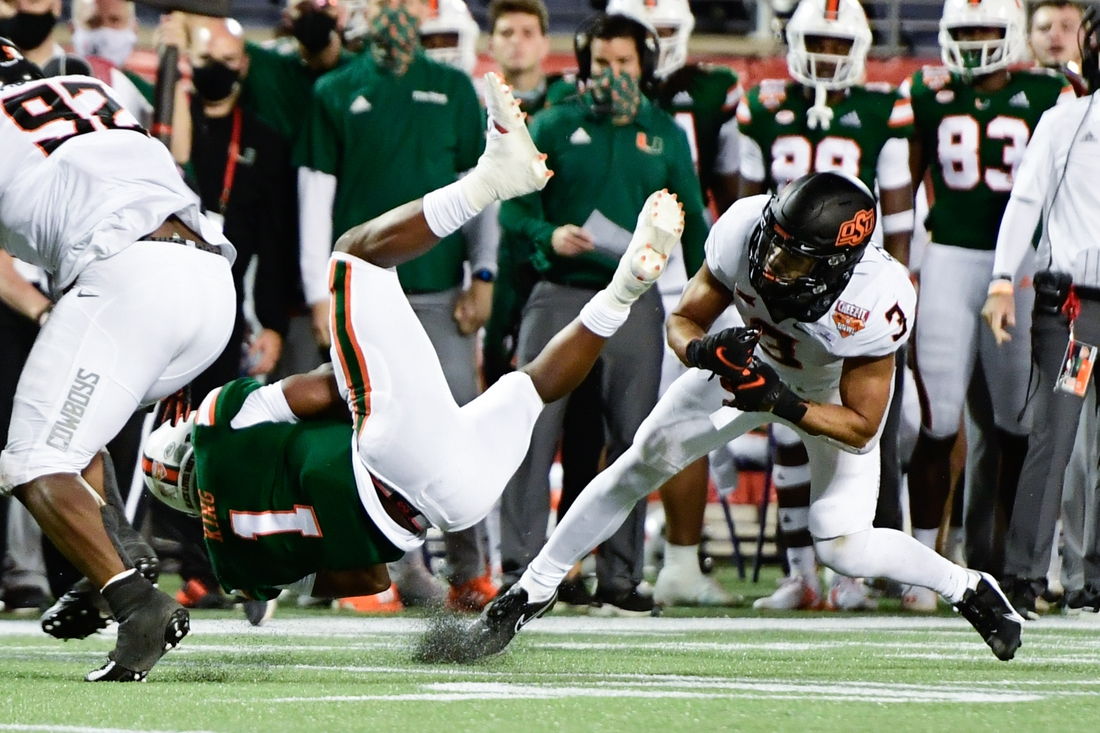 Dec 29, 2020; Orlando, FL, USA; Miami Hurricanes quarterback D'Eriq King (1) runs the ball before suffering an apparent injury on the play against Oklahoma State Cowboys safety Tre Sterling (3) during the first half of the Cheez-It Bowl Game at Camping World Stadium. Mandatory Credit: Douglas DeFelice-USA TODAY Sports