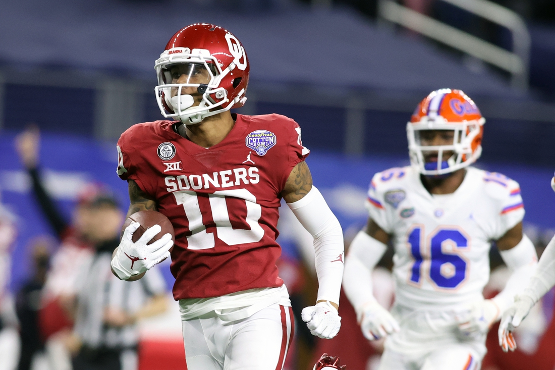 Dec 30, 2020; Arlington, TX, USA; Oklahoma Sooners wide receiver Theo Wease (10) runs for a touchdown after catching a pass against Florida Gators defensive back Tre'Vez Johnson (16) in the second quarter at ATT Stadium. Mandatory Credit: Tim Heitman-USA TODAY Sports
