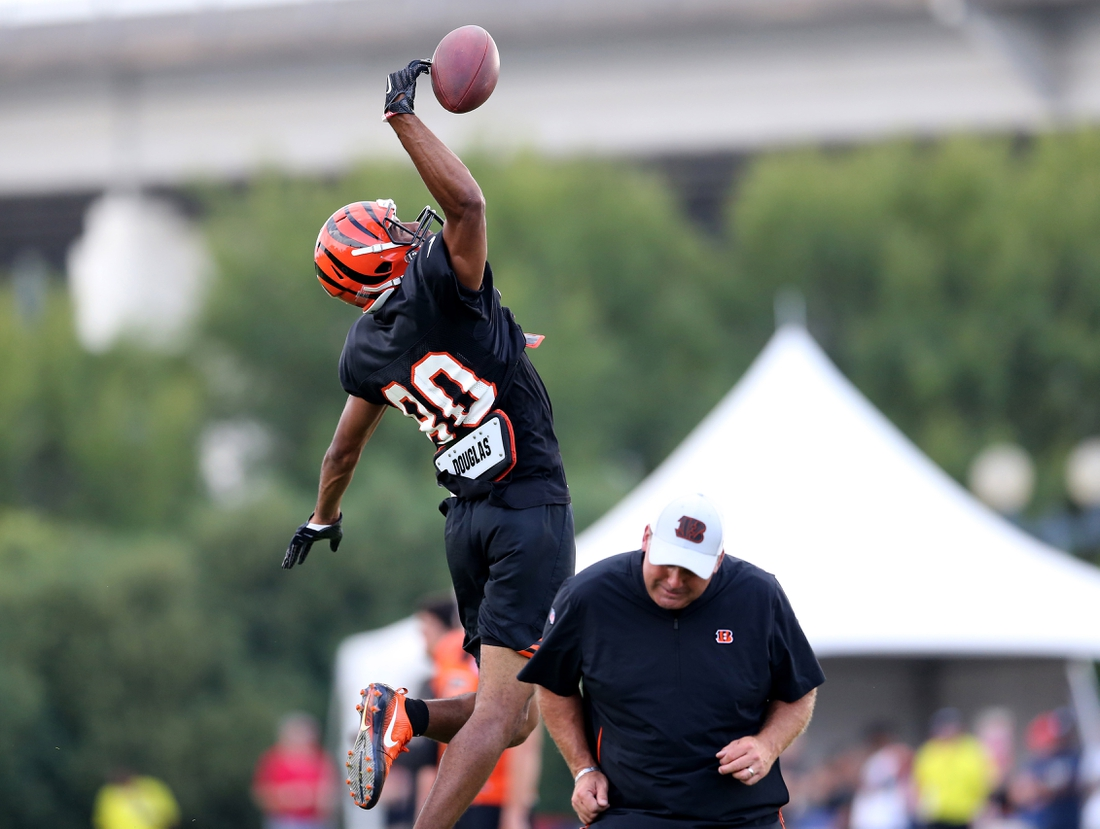 Aug 11, 2018; Cincinnati, OH, USA; Cincinnati Bengals wide receiver Josh Malone (80) goes up for a catch as Cincinnati Bengals wide receivers coach Bob Bicknell gets out of the way during Cincinnati Bengals training camp at the practice fields next to Paul Brown Stadium. Mandatory Credit: Kareem Elgazzar/The Cincinnati Enquirer via USA TODAY NETWORK