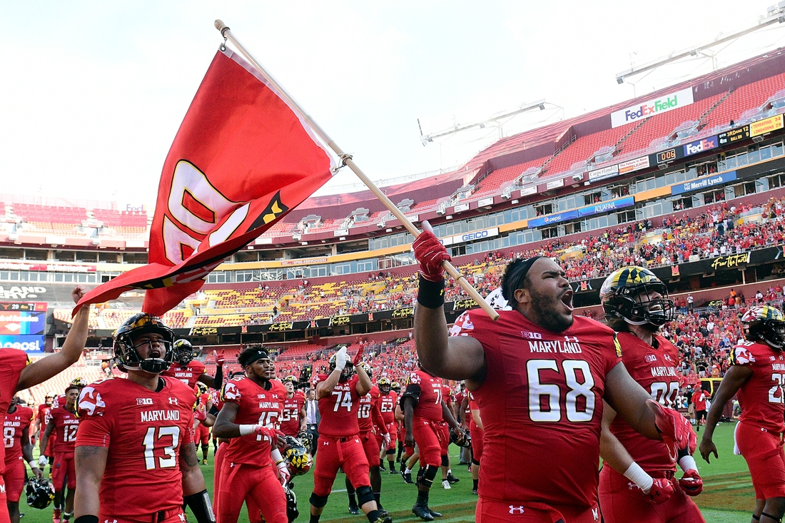 Sep 1, 2018; Landover, MD, USA;  Maryland Terrapins offensive lineman Ellis McKennie (68) runs onto the field with his teammates holding a flag in remembrance of Jordan McNair after defeating Texas Longhorns at FedEx Field. Mandatory Credit: Tommy Gilligan-USA TODAY Sports