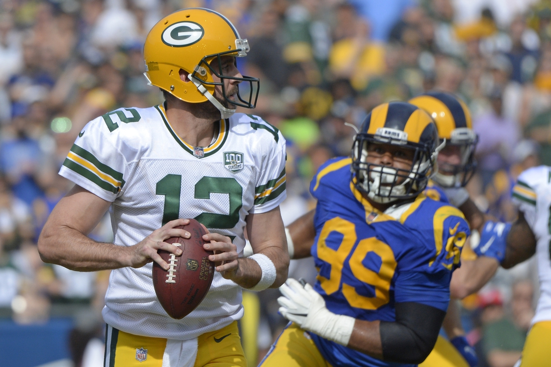 Oct 28, 2018; Los Angeles, CA, USA; Green Bay Packers quarterback Aaron Rodgers (12) looks to pass as Los Angeles Rams defensive tackle Aaron Donald (99) rushes during the first quarter at Los Angeles Memorial Coliseum. Mandatory Credit: Jake Roth-USA TODAY Sports