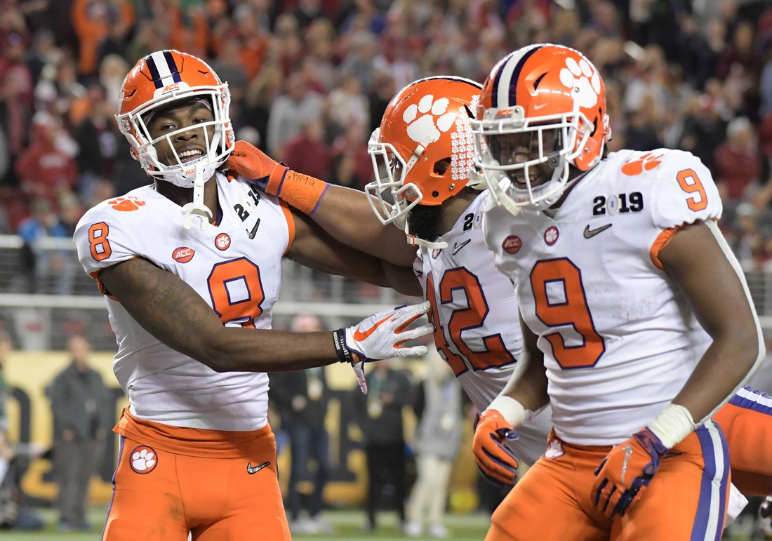 Jan 7, 2019; Santa Clara, CA, USA; Clemson Tigers wide receiver Justyn Ross (8) celebrates with defensive lineman Christian Wilkins (42) and running back Travis Etienne (9) after scoring against the Alabama Crimson Tide in the third quarter during the 2019 College Football Playoff Championship game at Levi's Stadium. Mandatory Credit: Kirby Lee-USA TODAY Sports