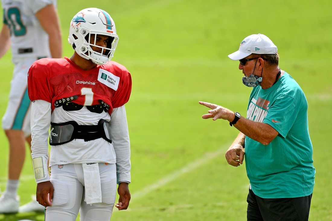 Aug 26, 2020; Miami Gardens, Florida, USA; Miami Dolphins quarterback Tua Tagovailoa (1) talks with offensive coordinator Chan Gailey (R) during training camp at Baptist Health Training Facility. Mandatory Credit: Jasen Vinlove-USA TODAY Sports