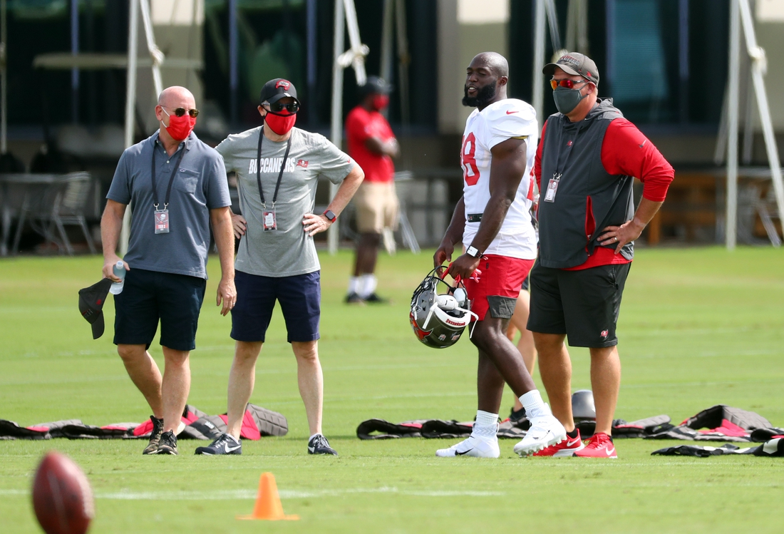 Sep 9, 2020; Tampa, Florida, United States;Tampa Bay Buccaneers running back Leonard Fournette (28) talks with general manager Jason Licht, owner Joel Glazer and owner Bryan Glazer at AdventHealth Training Center. Mandatory Credit: Kim Klement-USA TODAY Sports
