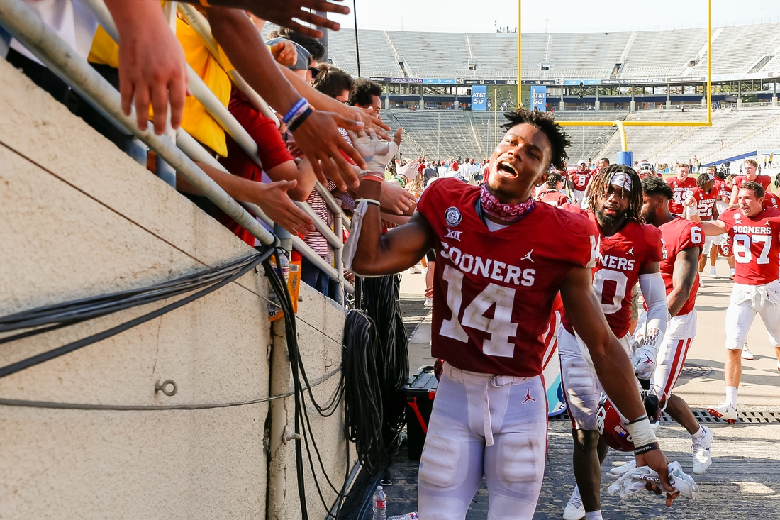 Oct 10, 2020; Dallas, Texas, USA; Oklahoma Sooners wide receiver Charleston Rambo (14) celebrates the win against the Texas Longhorns with fans after the Red River Showdown at Cotton Bowl. Mandatory Credit: Andrew Dieb-USA TODAY Sports