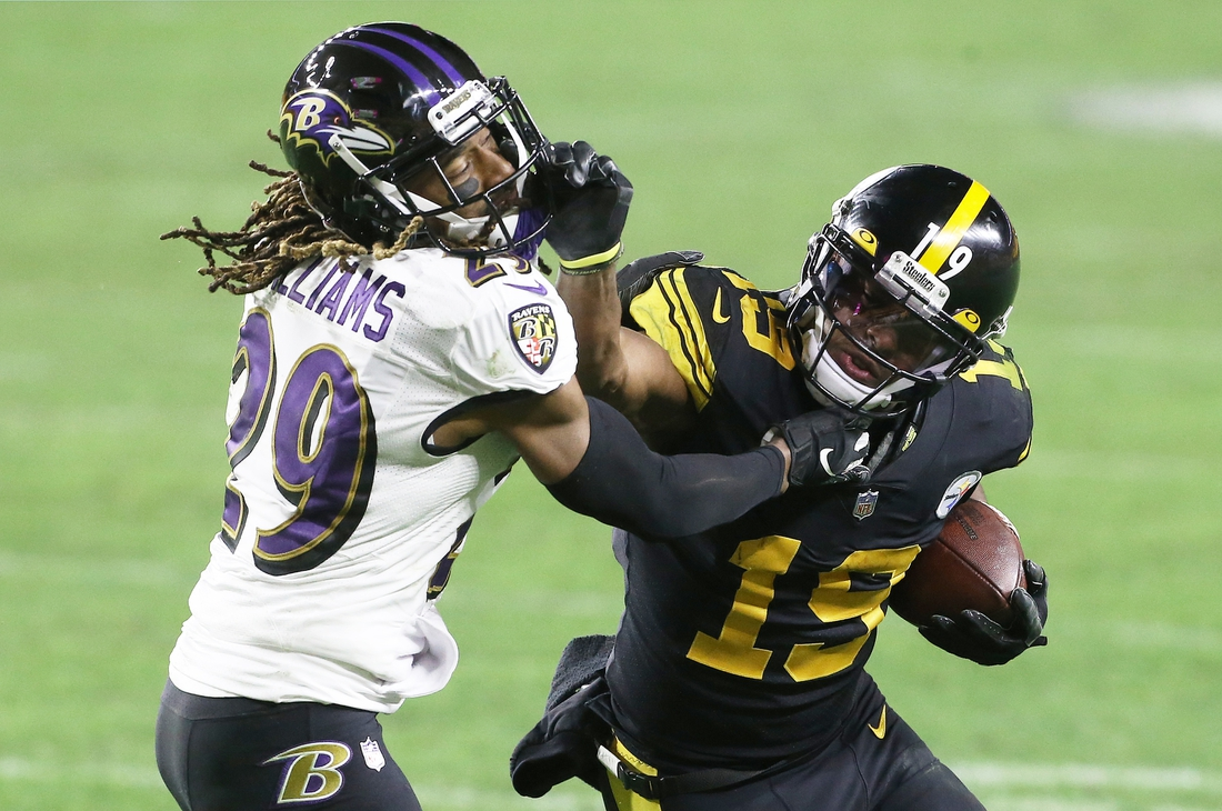 Dec 2, 2020; Pittsburgh, Pennsylvania, USA;  Pittsburgh Steelers wide receiver JuJu Smith-Schuster (19) runs after a catch against Baltimore Ravens cornerback Tramon Williams (29) during the fourth quarter at Heinz Field. Pittsburgh won 19-14.  Mandatory Credit: Charles LeClaire-USA TODAY Sports