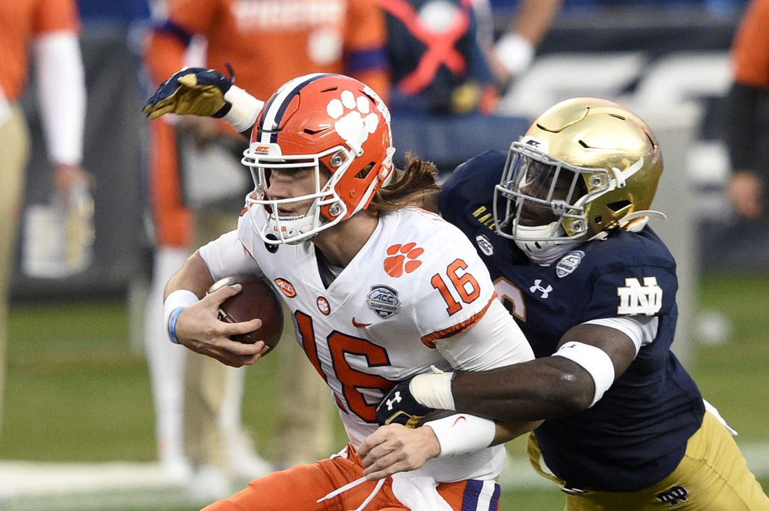 Dec 19, 2020; Charlotte, NC, USA; Clemson Tigers quarterback Trevor Lawrence (16) with the ball as Notre Dame Fighting Irish linebacker Jeremiah Owusu-Koramoah (6) defends in the second quarter at Bank of America Stadium. Mandatory Credit: Bob Donnan-USA TODAY Sports