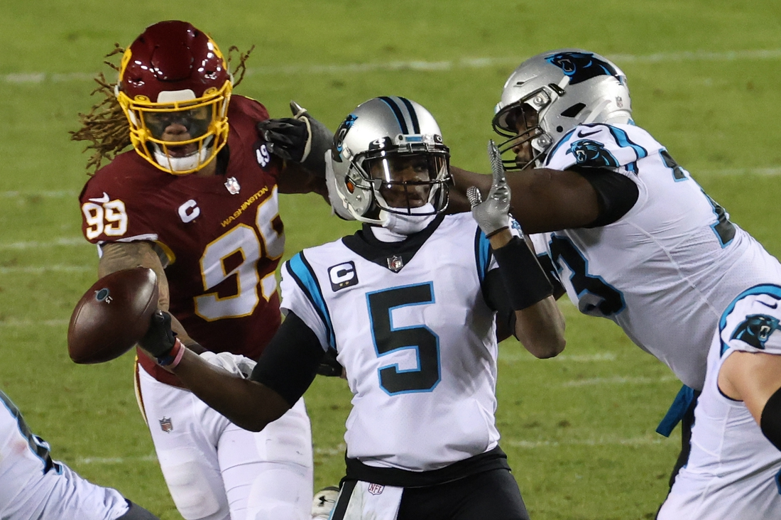Dec 27, 2020; Landover, Maryland, USA; Carolina Panthers quarterback Teddy Bridgewater (5) fumbles the ball on a hit by Washington Football Team defensive end Chase Young (99) in the second quarter at FedExField. Mandatory Credit: Geoff Burke-USA TODAY Sports