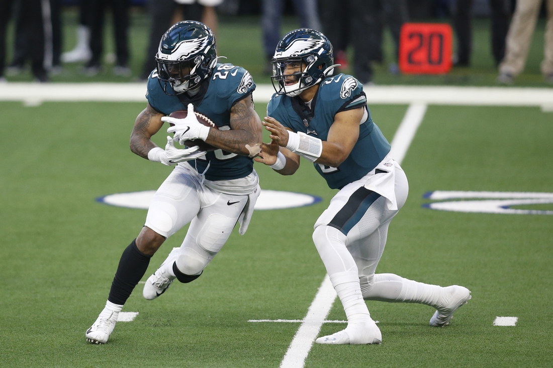 Dec 27, 2020; Arlington, Texas, USA; Philadelphia Eagles running back Miles Sanders (26) takes the handoff from quarterback Jalen Hurts (2) in the second quarter against the Dallas Cowboys at AT&T Stadium. Mandatory Credit: Tim Heitman-USA TODAY Sports