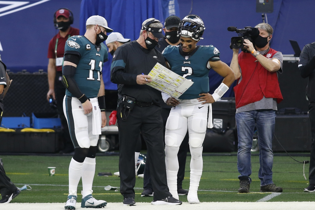 Dec 27, 2020; Arlington, Texas, USA; Philadelphia Eagles quarterbacks Carson Wentz (11) and Jalen Hurts (2) talk with head coach Doug Pederson (C) during a timeout against the Dallas Cowboys in the second quarter at AT&T Stadium. Mandatory Credit: Tim Heitman-USA TODAY Sports