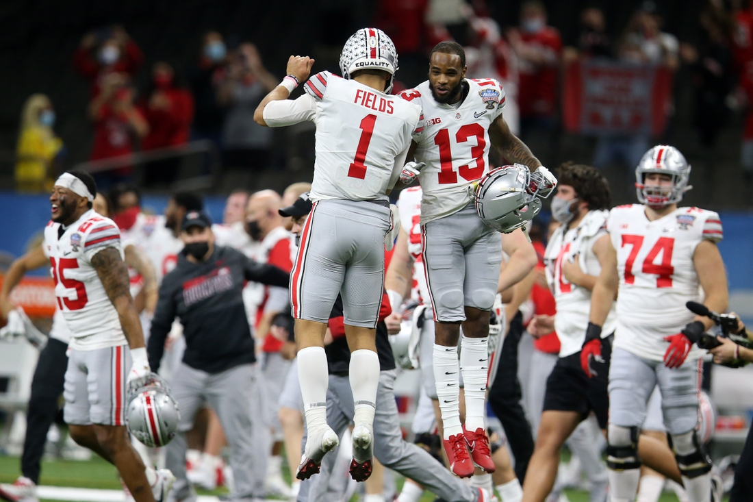 Jan 1, 2021; New Orleans, LA, USA; Ohio State Buckeyes quarterback Justin Fields (1) and Ohio State Buckeyes wide receiver Gee Scott Jr. (13) celebrate after defeating the Clemson Tigers at Mercedes-Benz Superdome. Mandatory Credit: Chuck Cook-USA TODAY Sports