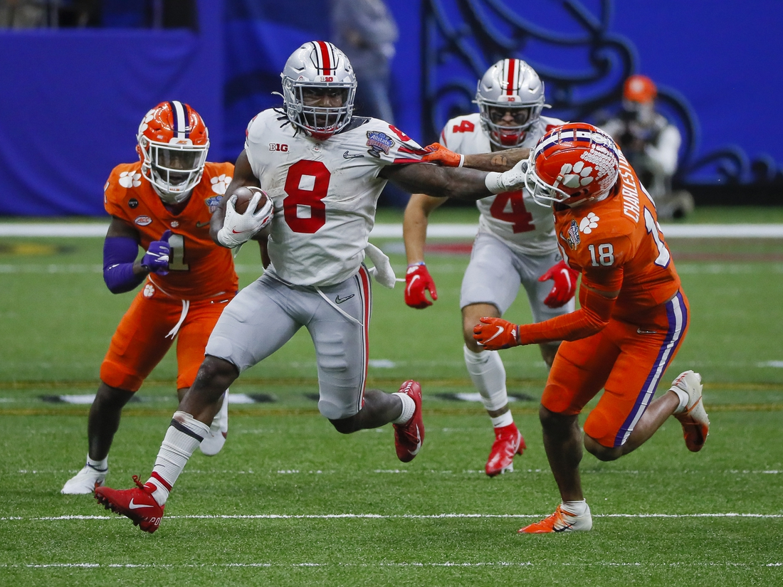 Jan 1, 2021; New Orleans, LA, USA; Ohio State Buckeyes running back Trey Sermon (8) grabs the face mask of Clemson Tigers safety Joseph Charleston (18) as he runs upfield during the fourth quarter of the College Football Playoff semifinal at the Allstate Sugar Bowl in the Mercedes-Benz Superdome in New Orleans on Friday, Jan. 1, 2021. Ohio State won 49-28.  Mandatory Credit: Adam Cairns-USA TODAY Sports