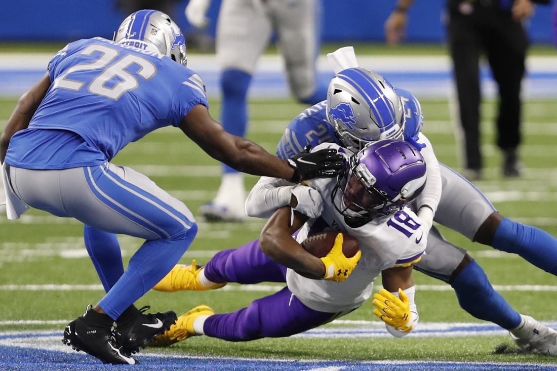 Jan 3, 2021; Detroit, Michigan, USA; Minnesota Vikings wide receiver Justin Jefferson (18) gets tackled by Detroit Lions cornerback Amani Oruwariye (24) and strong safety Duron Harmon (26) during the first quarter at Ford Field. Mandatory Credit: Raj Mehta-USA TODAY Sports