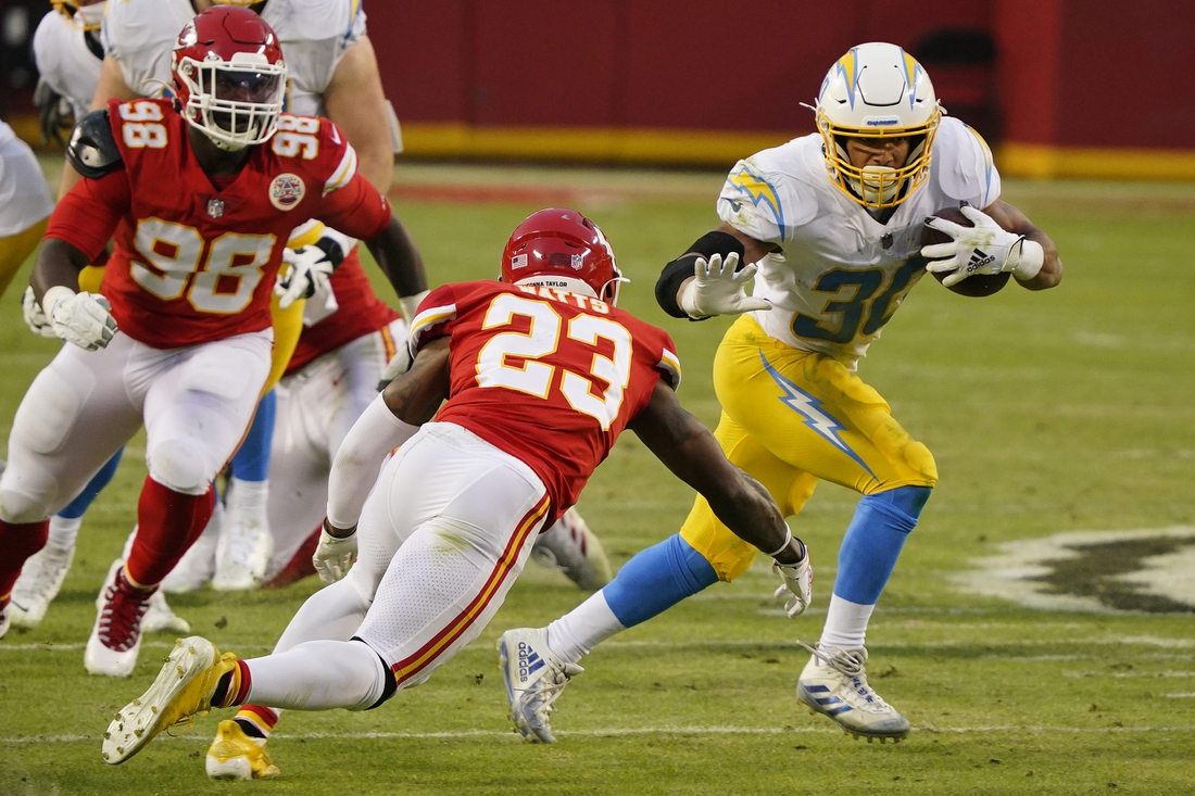 Jan 3, 2021; Kansas City, Missouri, USA; Los Angeles Chargers running back Austin Ekeler (30) runs the ball against Kansas City Chiefs defensive tackle Tershawn Wharton (98) and safety Armani Watts (23) during the first half at Arrowhead Stadium. Mandatory Credit: Jay Biggerstaff-USA TODAY Sports