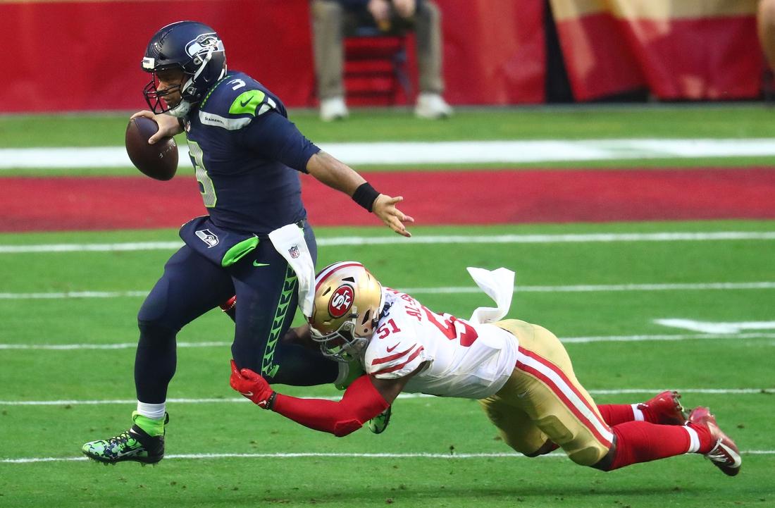 Jan 3, 2021; Glendale, Arizona, USA; Seattle Seahawks quarterback Russell Wilson (3) runs the ball against San Francisco 49ers linebacker Azeez Al-Shaair (51) during the second half at State Farm Stadium. Mandatory Credit: Mark J. Rebilas-USA TODAY Sports