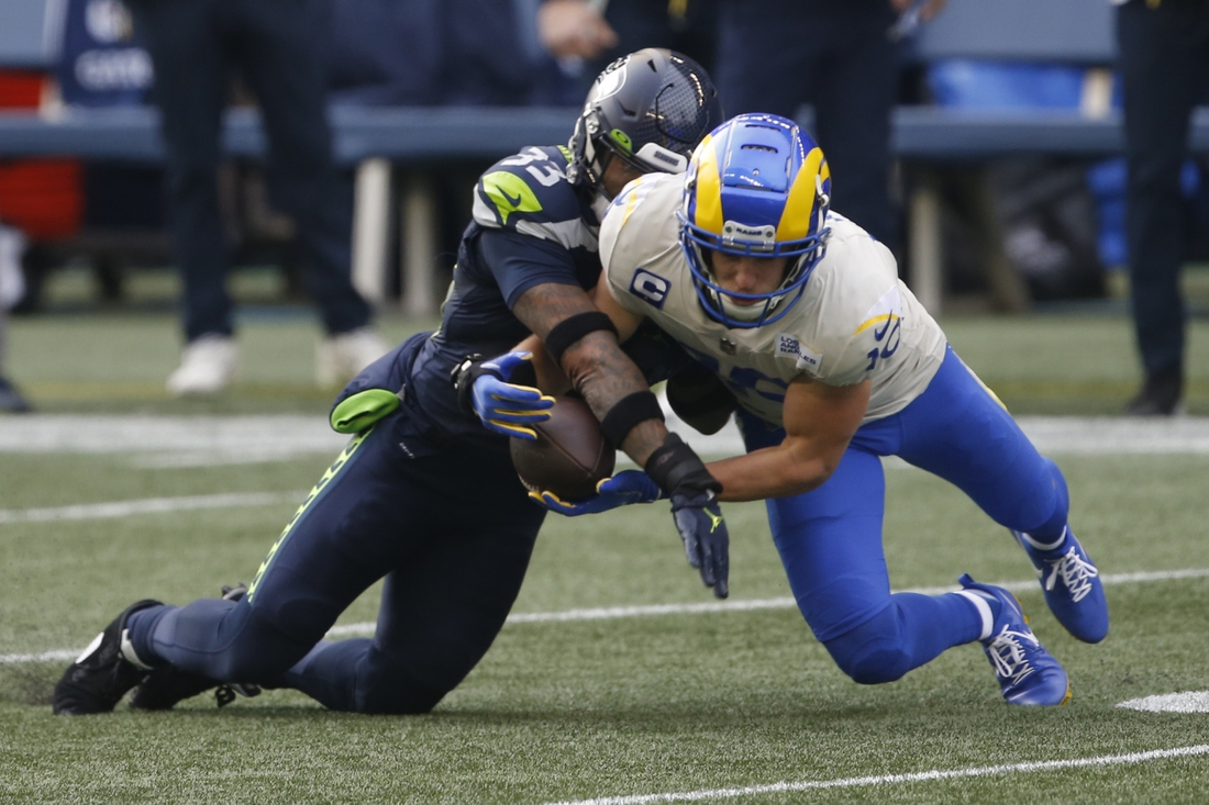 Jan 9, 2021; Seattle, Washington, USA; Los Angeles Rams wide receiver Cooper Kupp (10) catches a ball while under pressure by Seattle Seahawks safety Jamal Adams (33)  during the first quarter at Lumen Field. Mandatory Credit: Joe Nicholson-USA TODAY Sports