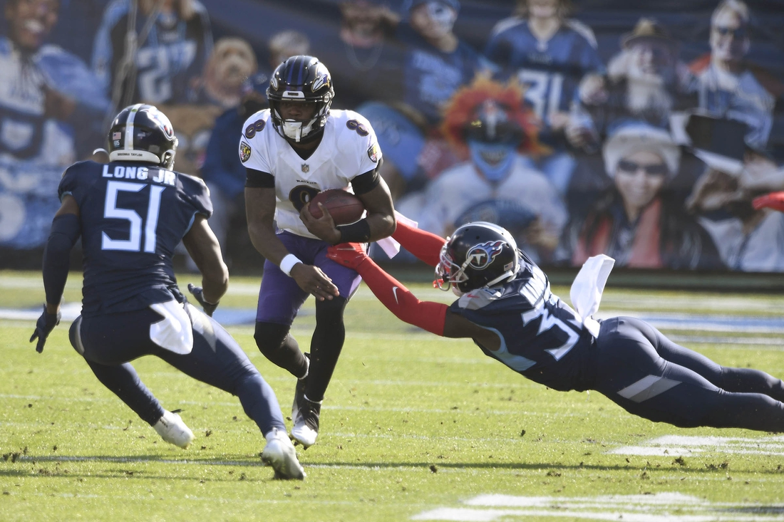 Jan 10, 2021; Nashville, Tennessee, USA; Tennessee Titans linebacker David Long Jr., (51) and cornerback Desmond King II (33) stop Baltimore Ravens quarterback Lamar Jackson (8) during the Tennessee Titans game against the Baltimore Ravens. Mandatory Credit: George Walker/The Tennessean via USA TODAY Sports