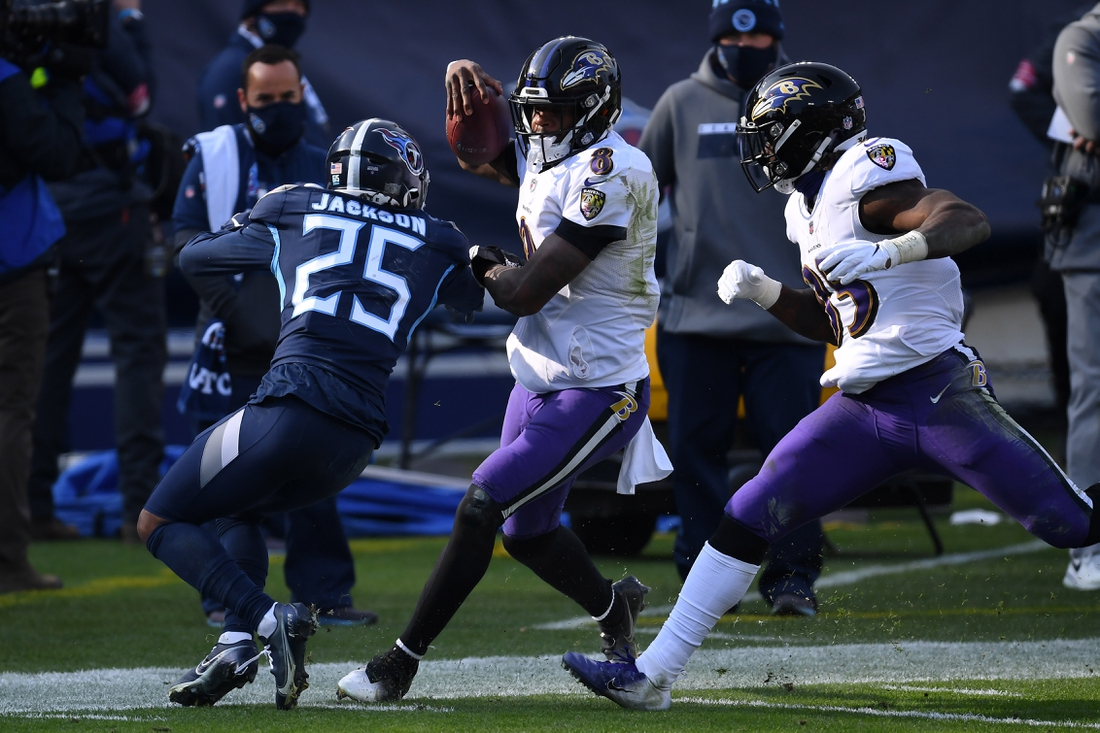 Jan 10, 2021; Nashville, Tennessee, USA; Baltimore Ravens quarterback Lamar Jackson (8) runs with the ball while defended by Tennessee Titans cornerback Adoree' Jackson (25) during the third quarter in a AFC Wild Card playoff game at Nissan Stadium. Mandatory Credit: Christopher Hanewinckel-USA TODAY Sports