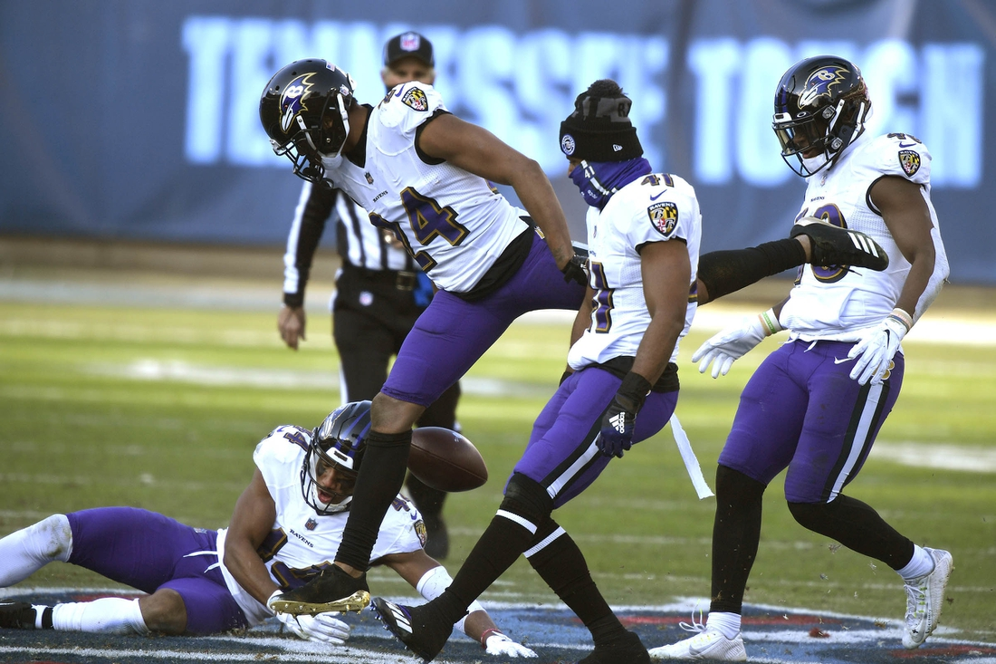 Jan 10, 2021; Nashville, Tennessee, USA; Baltimore Ravens cornerback Marcus Peters (24) and his teammates stomp on the Titans logo after Peters intercepted the ball to seal their victory over Tennessee in Nashville. Mandatory Credit: George Walker/The Tennessean via USA TODAY Sports