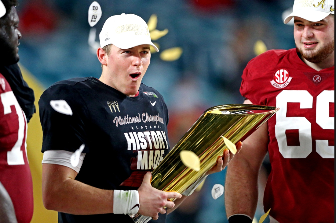 Jan 11, 2021; Miami Gardens, Florida, USA; Alabama Crimson Tide quarterback Mac Jones (10) celebrates with the CFP National Championship trophy after beating the Ohio State Buckeyes in the 2021 College Football Playoff National Championship Game. Mandatory Credit: Mark J. Rebilas-USA TODAY Sports