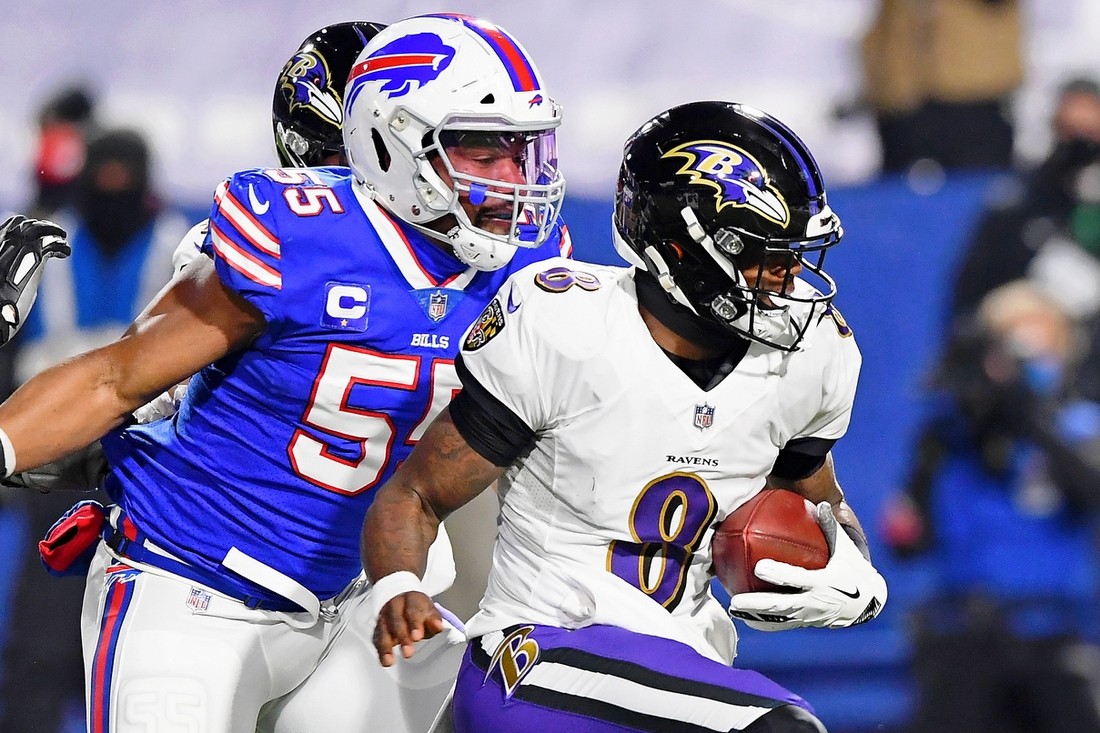 Jan 16, 2021; Orchard Park, New York, USA; Baltimore Ravens quarterback Lamar Jackson (8) runs with the ball as Buffalo Bills defensive end Jerry Hughes (55) pursues during the first half of an AFC Divisional Round playoff game at Bills Stadium. Mandatory Credit: Rich Barnes-USA TODAY Sports