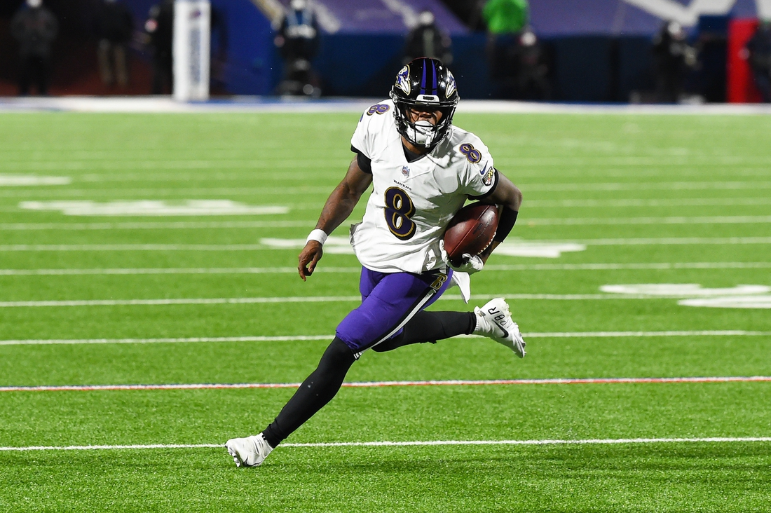 Jan 16, 2021; Orchard Park, New York, USA; Baltimore Ravens quarterback Lamar Jackson (8) runs with the ball against the Buffalo Bills during the third quarter of an AFC Divisional Round game at Bills Stadium. Mandatory Credit: Rich Barnes-USA TODAY Sports