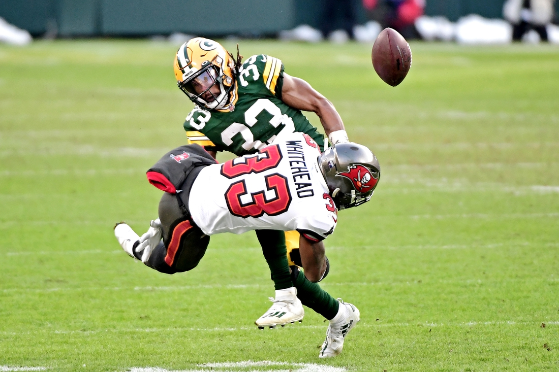 Jan 24, 2021; Green Bay, Wisconsin, USA; Tampa Bay Buccaneers free safety Jordan Whitehead (33) forces a fumble by Green Bay Packers running back Aaron Jones (33) during the third quarter in the NFC Championship Game at Lambeau Field . Mandatory Credit: Benny Sieu-USA TODAY Sports
