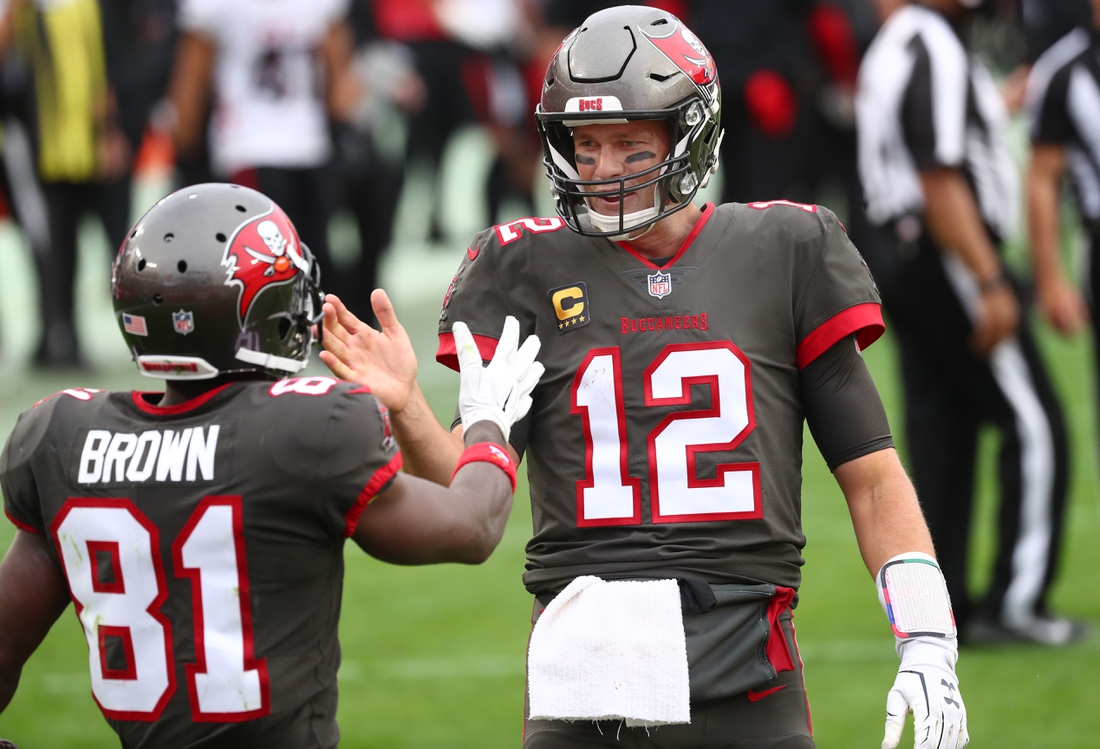 Jan 3, 2021; Tampa, Florida, USA; Tampa Bay Buccaneers quarterback Tom Brady (12) smiles with wide receiver Antonio Brown (81) after he scored a touchdown against the Atlanta Falcons during the second half at Raymond James Stadium. Mandatory Credit: Kim Klement-USA TODAY Sports