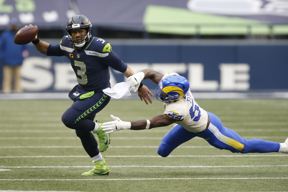 Jan 9, 2021; Seattle, Washington, USA; Seattle Seahawks quarterback Russell Wilson (3) avoids the tackle by Los Angeles Rams linebacker Leonard Floyd (54) during the third quarter at Lumen Field. Mandatory Credit: Joe Nicholson-USA TODAY Sports