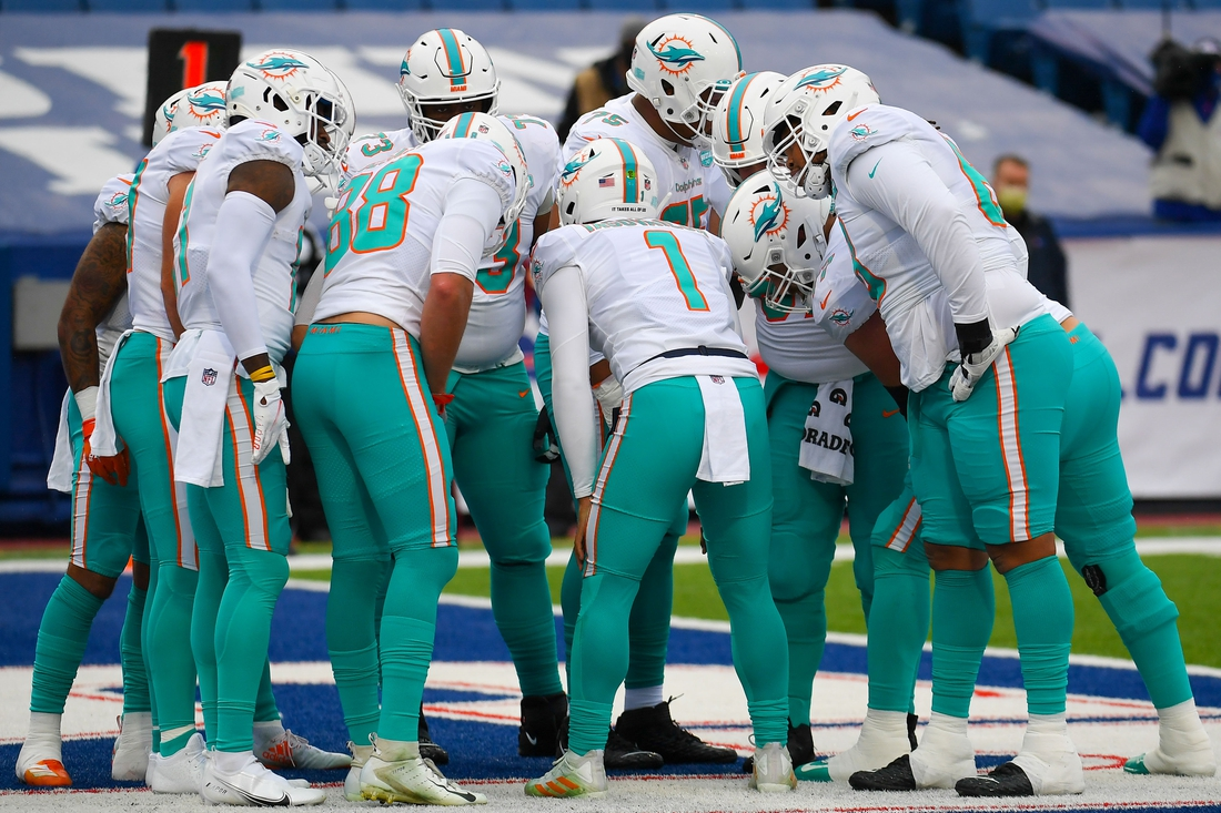 Jan 3, 2021; Orchard Park, New York, USA; Miami Dolphins quarterback Tua Tagovailoa (1) calls a play in the huddle against the Buffalo Bills during the first quarter at Bills Stadium. Mandatory Credit: Rich Barnes-USA TODAY Sports