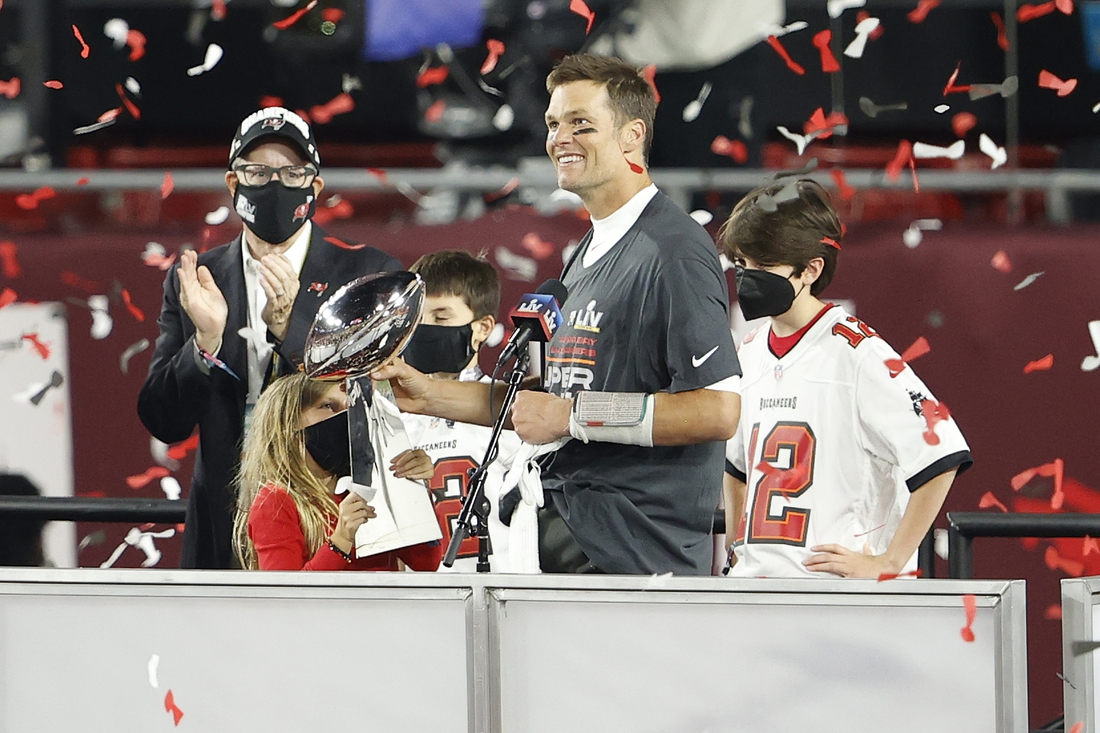 Feb 7, 2020; Tampa, FL, USA; Tampa Bay Buccaneers quarterback Tom Brady (12) hands the Lombardi Trophy to his children after Super Bowl LV at Raymond James Stadium.  Mandatory Credit: Kim Klement-USA TODAY Sports