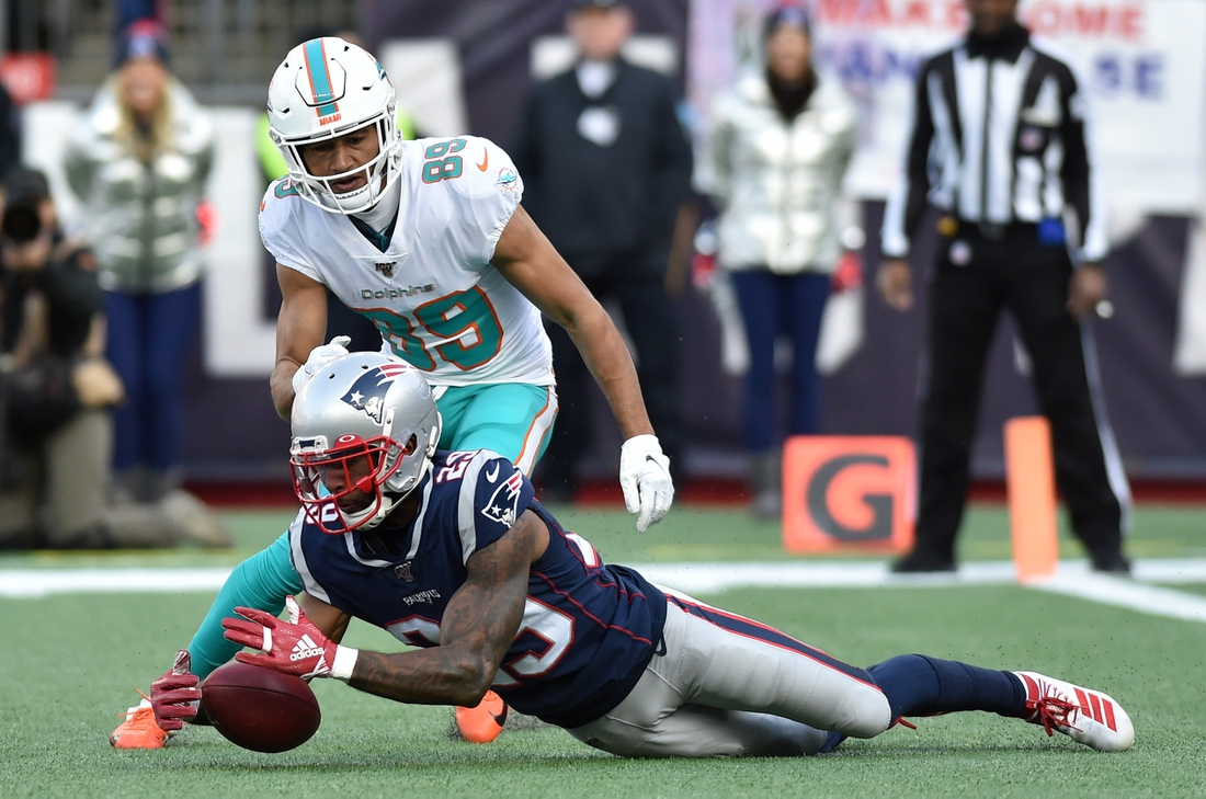 Dec 29, 2019; Foxborough, Massachusetts, USA;  New England Patriots defensive back Justin Bethel (29) downs a punt inside the 5 yard line while Miami Dolphins wide receiver Trevor Davis (89) looks on during the first half at Gillette Stadium. Mandatory Credit: Bob DeChiara-USA TODAY Sports