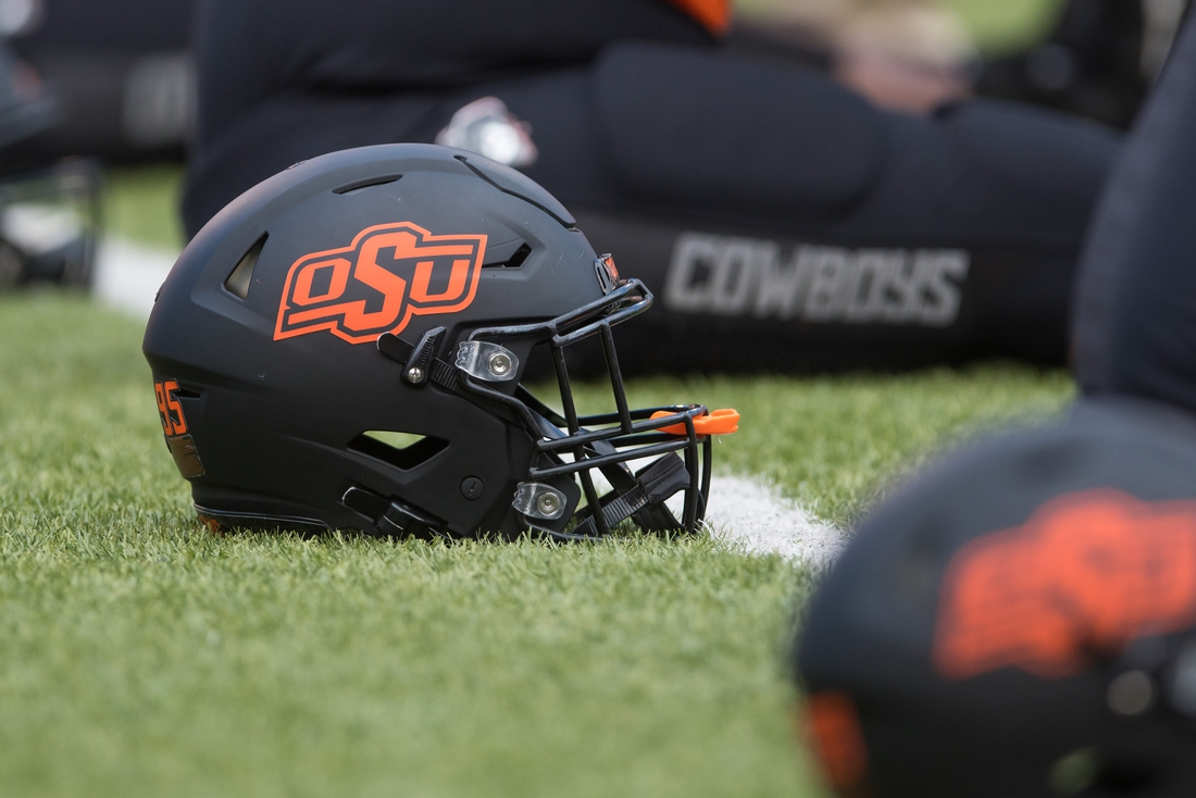 Oct 31, 2020; Stillwater, Oklahoma, USA;  Oklahoma State Cowboys helmets lie on the field as players stretch before a game against the Texas Longhorns at Boone Pickens Stadium. Mandatory Credit: Brett Rojo-USA TODAY Sports