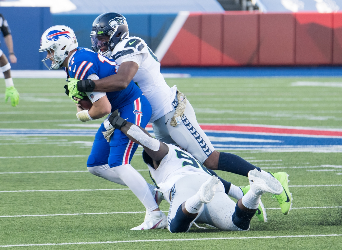 Nov 8, 2020; Orchard Park, New York, USA; Buffalo Bills quarterback Josh Allen (17) is sacked by Seattle Seahawks defensive end Carlos Dunlap II (top) and defensive tackle Jarran Reed (90) in the third quarter at Bills Stadium. Mandatory Credit: Mark Konezny-USA TODAY Sports
