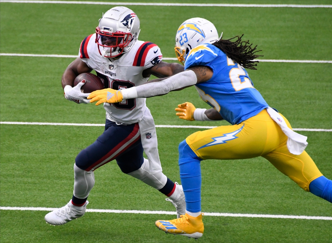 Dec 6, 2020; Inglewood, California, USA; New England Patriots running back James White (28) tries to break free from  Los Angeles Chargers free safety Nasir Adderley (24) during the second quarter at SoFi Stadium. Mandatory Credit: Robert Hanashiro-USA TODAY Sports