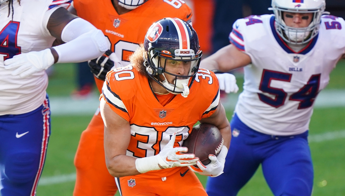 Dec 19, 2020; Denver, Colorado, USA; Denver Broncos running back Phillip Lindsay (30) runs against Buffalo Bills linebacker A.J. Klein (54) during the first quarter at Empower Field at Mile High. Mandatory Credit: Troy Babbitt-USA TODAY Sports
