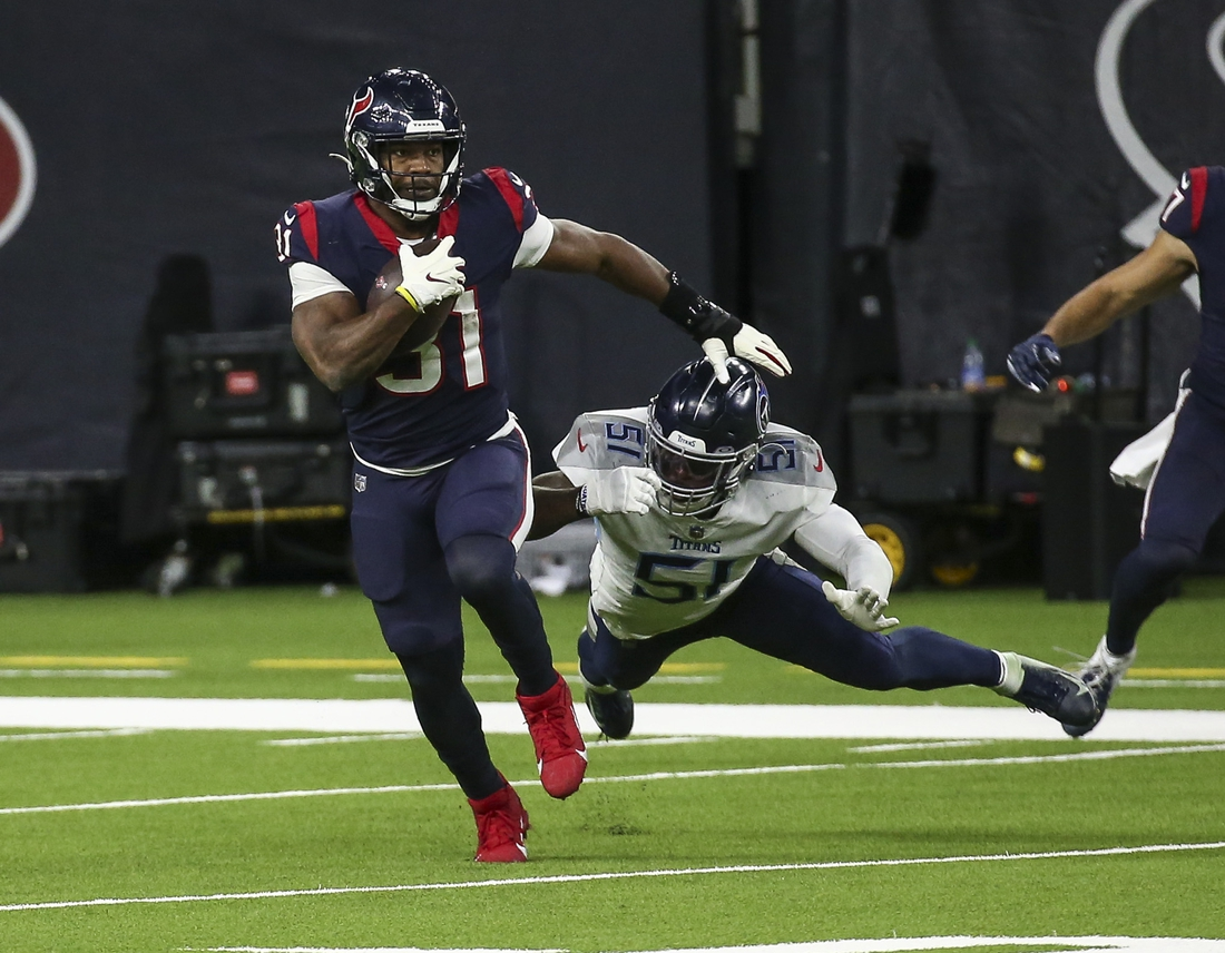 Jan 3, 2021; Houston, Texas, USA; Houston Texans running back David Johnson (31) runs with the ball as Tennessee Titans linebacker David Long (51) attempts to make a tackle during the fourth quarter at NRG Stadium. Mandatory Credit: Troy Taormina-USA TODAY Sports
