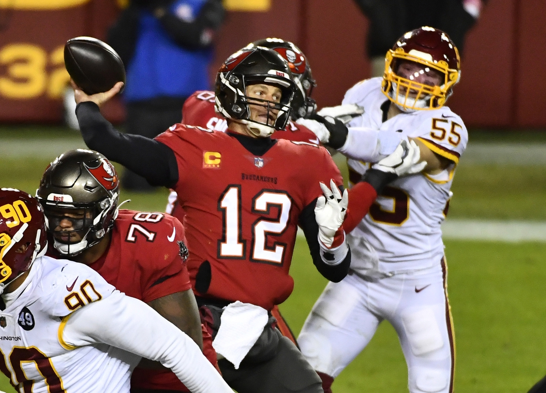 Jan 9, 2021; Landover, Maryland, USA; Tampa Bay Buccaneers quarterback Tom Brady (12) throws a pass as Washington Football Team linebacker Cole Holcomb (55) rushes during the third quarter at FedExField. Mandatory Credit: Brad Mills-USA TODAY Sports