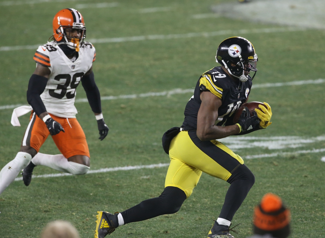 Jan 10, 2021; Pittsburgh, PA, USA; Pittsburgh Steelers wide receiver JuJu Smith-Schuster (19) runs the ball past Cleveland Browns cornerback Terrance Mitchell (39) in the third quarter of an AFC Wild Card playoff game at Heinz Field. Mandatory Credit: Charles LeClaire-USA TODAY Sports