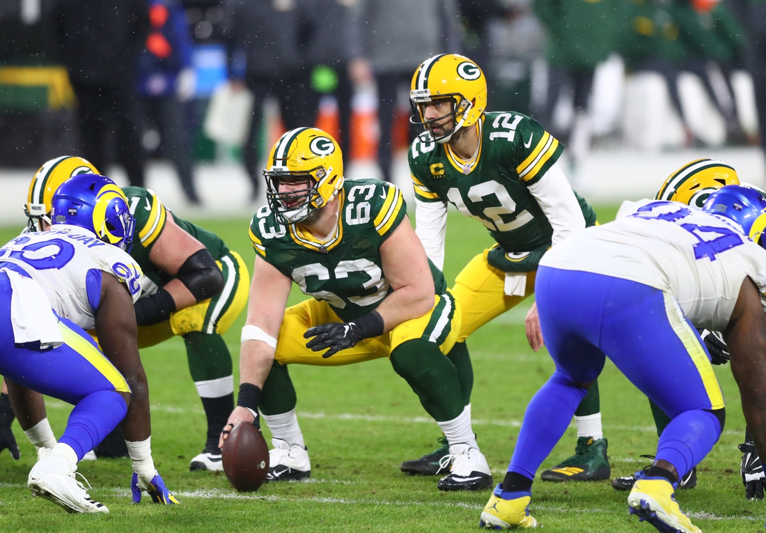 Jan 16, 2021; Green Bay, Wisconsin, USA; Green Bay Packers center Corey Linsley (63) prepares to snap the ball to quarterback Aaron Rodgers (12) against the Los Angeles Rams during the NFC Divisional Round at Lambeau Field. Mandatory Credit: Mark J. Rebilas-USA TODAY Sports
