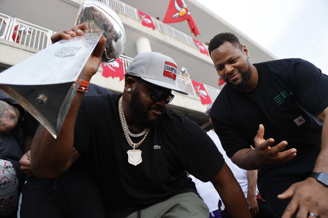 Feb 10, 2021; Tampa Bay, FL, USA;  Tampa Bay Buccaneers offensive tackle Donovan Smith (left) and defensive end Ndamukong Suh dance with the Vince Lombardi Trophy during a boat parade to celebrate victory in Super Bowl LV against the Kansas City Chiefs. Mandatory Credit: Kim Klement-USA TODAY Sports