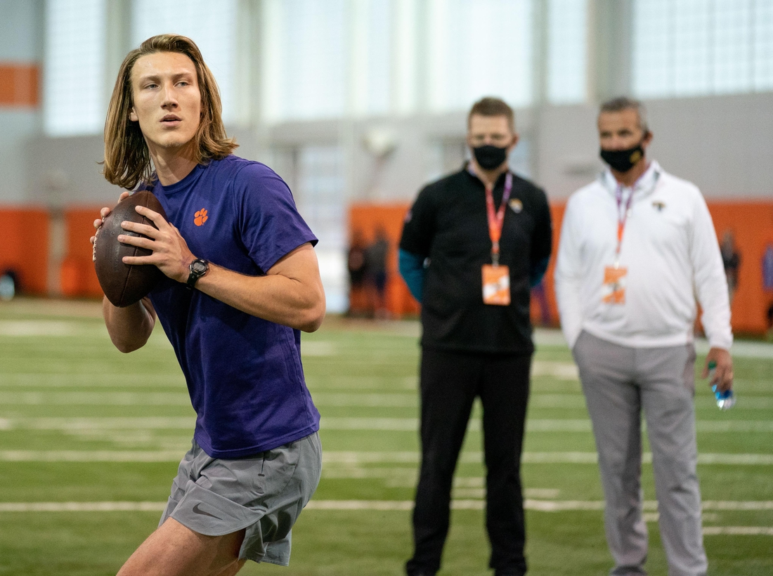 Feb 12, 2021; Clemson, SC, USA;  Clemson Tigers quarterback Trevor Lawrence works out as Jacksonville Jaguars head coach Urban Meyer (right) looks on during Pro Day in Clemson, South Carolina. Mandatory Credit: David Platt/Handout Photo via USA TODAY Sports