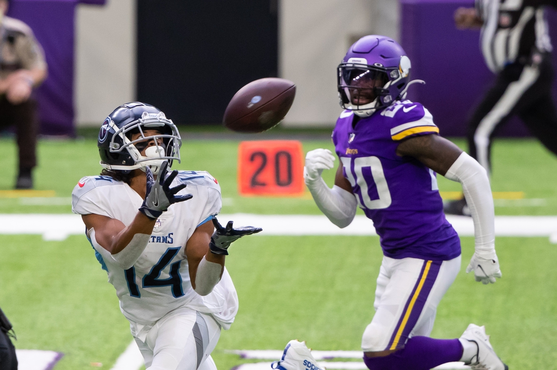 Sep 27, 2020; Minneapolis, Minnesota, USA; Tennessee Titans wide receiver Kalif Raymond (14) catches a pass in the third quarter against the Minnesota Vikings defensive back Jeff Gladney (20) at U.S. Bank Stadium. Mandatory Credit: Brad Rempel-USA TODAY Sports