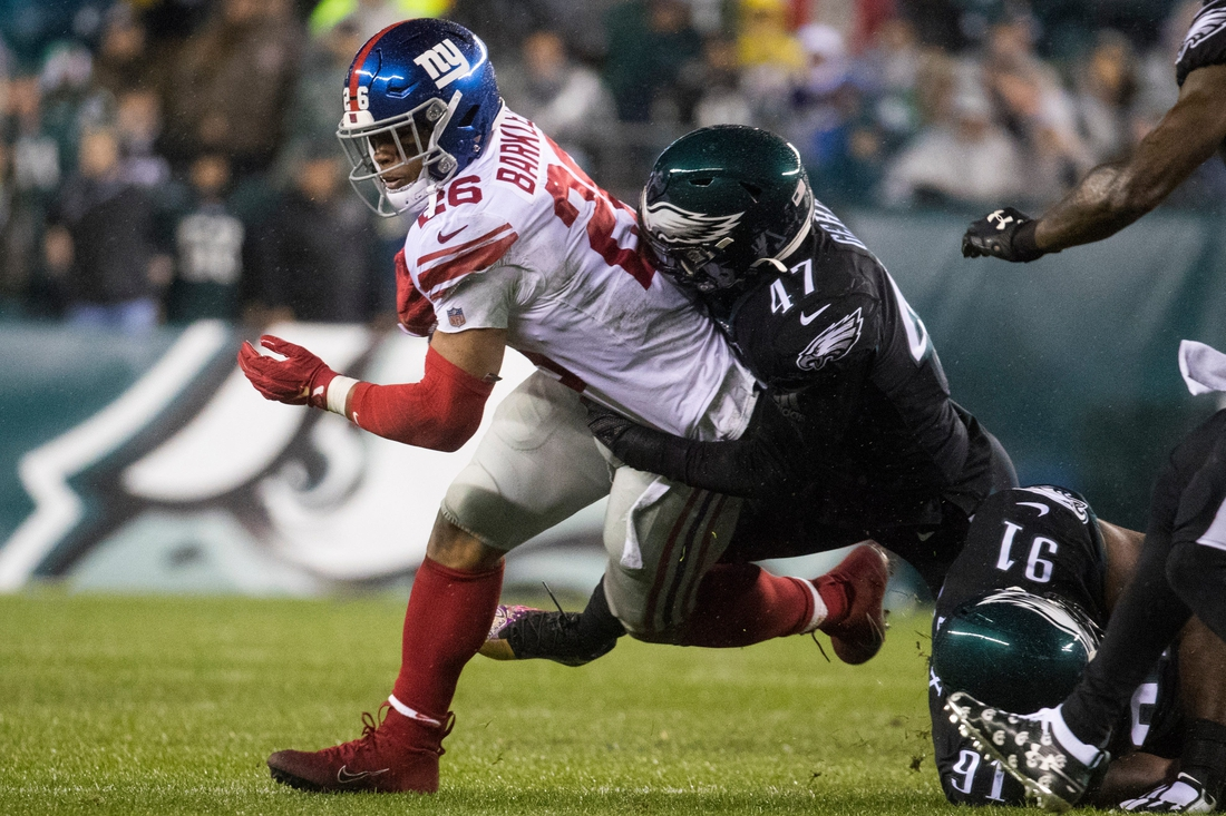 New York's Saquon Barkley (26) is brought down by Philadelphia's Nathan Gerry.  Sports Eagles Giants