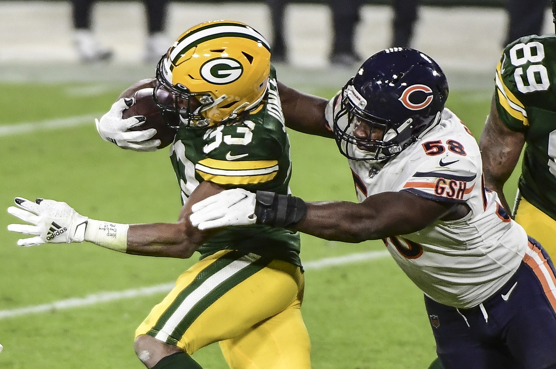 Nov 29, 2020; Green Bay, Wisconsin, USA;  Green Bay Packers running back Aaron Jones (33) tries to break a tackle by Chicago Bears linebacker Roquan Smith (58) in the fourth quarter at Lambeau Field. Mandatory Credit: Benny Sieu-USA TODAY Sports