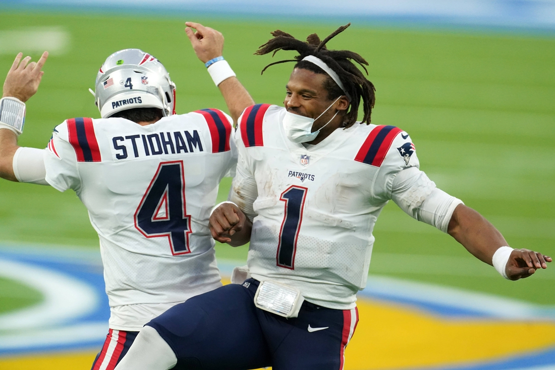 Dec 6, 2020; Inglewood, California, USA; New England Patriots quarterback Cam Newton (1) and quarterback Jarrett Stidham (4) celebrate after a touchdown in the fourth quarter against the Los Angeles Chargers at SoFi Stadium. Mandatory Credit: Kirby Lee-USA TODAY Sports