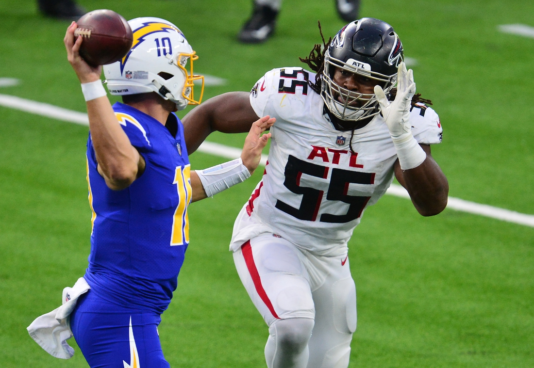 Dec 13, 2020; Inglewood, California, USA; Los Angeles Chargers quarterback Justin Herbert (10) throws under pressure against Atlanta Falcons defensive end Steven Means (55) during the second half at SoFi Stadium. Mandatory Credit: Gary A. Vasquez-USA TODAY Sports