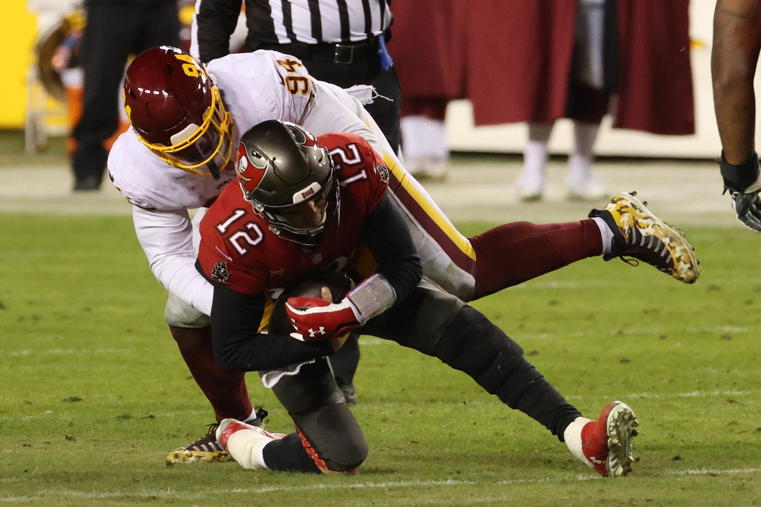 Jan 9, 2021; Landover, Maryland, USA; Tampa Bay Buccaneers quarterback Tom Brady (12) is sacked by Washington Football Team nose tackle Daron Payne (94) in the fourth quarter at FedExField. Mandatory Credit: Geoff Burke-USA TODAY Sports